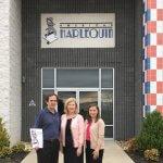 David Keary, Mona Nicholas and Elizabeth VanDeburg stand in front of American Harlequin headquarters.